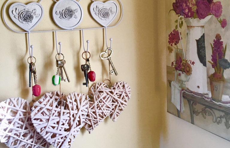 Pink ranunculus, open notebook, headphones on dark wooden background. Pastel colors, greeting card, toned vintage